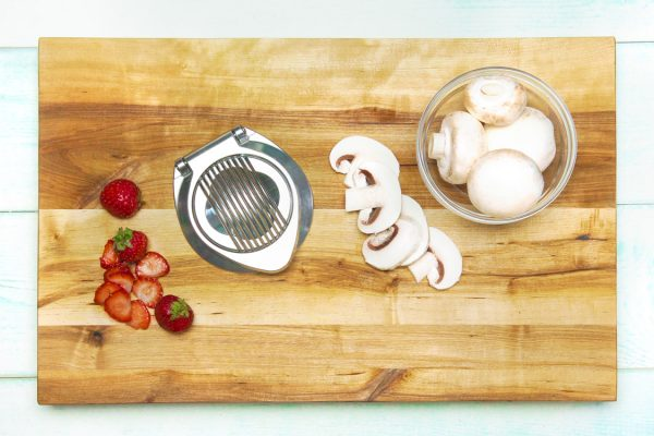 Slices of strawberries and mushrooms with an egg slicer on a cutting board