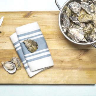 A closed oyster on a cloth on a cutting board
