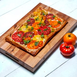 HEIRLOOM TOMATO TART Serves 6 to 8 Ingredients: 1 ¼ cups (310 ml) goat cheese (Dussa's Ham & Cheese Ltd.) 2 tbsp (30 ml) whipping cream (The Milkman) 1 tbsp (15 ml) chopped fresh basil leaves, plus extra for garnish (any produce vendor) 1 tbsp (15 ml) chopped fresh chives, plus extra for garnish (any produce vendor) ½ tsp (2.5 ml) finely grated lemon zest (any produce vendor) 10 sheets of phyllo dough, trimmed to size of baking tray 1/3 cup (70 ml) extra-virgin olive oil, divided (Vancouver Olive Oil Company) 9 tbsp (135 ml) plain breadcrumbs, divided 1 to 2 lbs (454 g to 907 g) mixed heirloom tomatoes, thinly sliced (any produce vendor) Salt and freshly ground pepper, to taste (The Grainry) Directions: 1. Preheat oven to 375°F (190°C). Line a large rimmed baking tray with parchment paper and set aside. 2. In a medium bowl, stir together goat cheese, whipping cream, basil, chives, and lemon zest until well combined. 3. Lay one sheet of phyllo on baking sheet, keeping remaining phyllo covered with a damp kitchen towel to prevent them from drying out. Brush lightly with olive oil and sprinkle all over with about 1 tablespoon of breadcrumbs. Repeat layering with remaining phyllo, olive oil, and breadcrumbs. Finish top layer with only a brushing of oil. 4. Spread goat cheese mixture evenly over top of layered phyllo dough, leaving a 1-inch border around edges. Artfully arrange tomato slices on top of goat cheese mixture. 5. Bake until phyllo is golden brown and crisp, about 25 to 30 minutes. Season with salt and pepper to taste before garnishing with additional chopped chives and basil leaves. Cut into squares and serve.